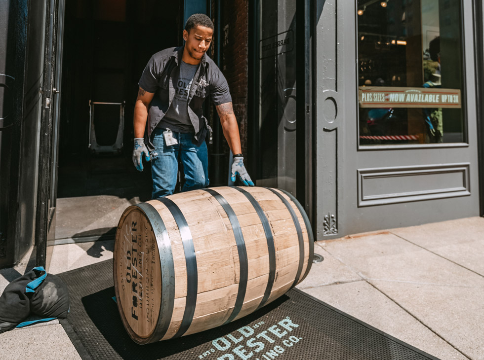 Man rolling Old Forester barrel out of Distillery