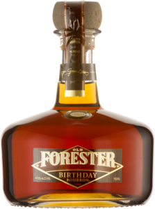 A bottle of Old Forester 2010 Birthday Bourbon on a black background.